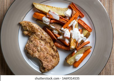 A simple, inexpensive meal: grilled chicken, roasted carrots and potatoes with a garlic sour cream sauce