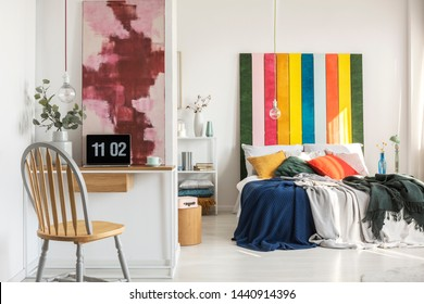 Simple lamp above desk with laptop and vase with flower in fashionable bedroom interior with lot of colors