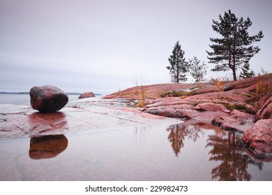 Simple landscape with big rock and trees reflected in a shallow pool at a granite shore of Ladoga lake, Karelia, Russia
