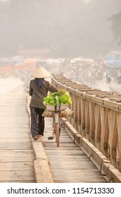 Simple life. Rear view of Vietnamese women with bicycle across the wooden bridge. Vietnamese women with Vietnam hat, vegetable on the bicycle. Rural of north Vietnam. Warm tone. Shallow dept of field.