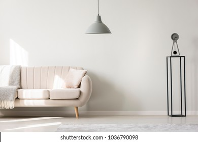 Simple living room interior with gray blanket on beige settee with a pillow standing against white wall