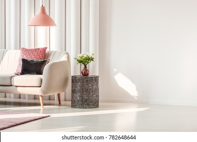Simple living room interior with pink and gray cushions on beige sofa and roses on metal table
