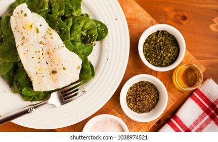 Simple Lunch of Organic Spinach on White Plate and placed on Wooden Chopping Board, with small herb bowls and pink Salt, plus oil