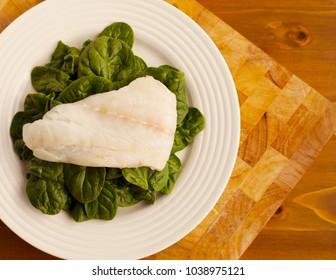 Simple Lunch of Organic Spinach on White Plate and placed on Wooden Chopping Board