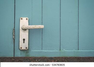 Simple metal door handle on a teal painted wooden door.