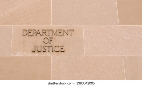 Simple Metal Letters on a Granite Wall Spelling out Department of Justice