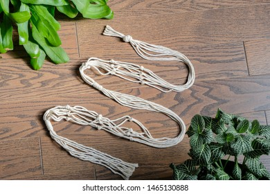 A simple minimalist cotton macrame plant hanger is laying on a hardwood floor with plants next to it. The macrame is 100 percent natural cotton and is handmade.