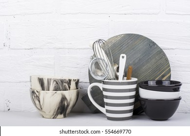 Simple modern kitchen still life in monochrome marble bowls, gray striped circle, round cutting board, ceramic bowls against a white brick wall. The horizontal.