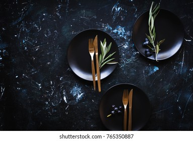 Simple modern kitchen still life in black ceramic plate bowls against a black brick wall with olive tree still life