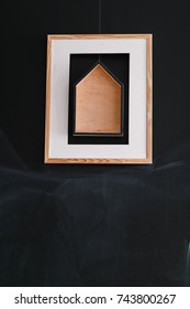 Simple modern square paintings with wooden house hanging on raw black wall