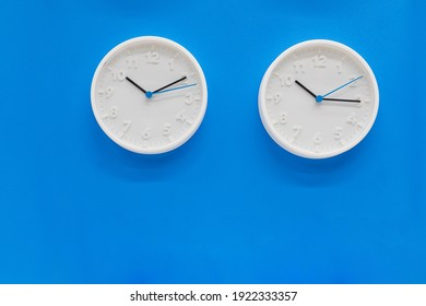 Simple modern wall clocks in white color frame, isolated on blue background.House Interior .big round clock hanging on a wall. copy space, deadline,time management concept and lunch time.