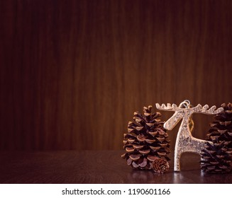 Simple, natural Christmas background with a rustic wooden moose ornament.