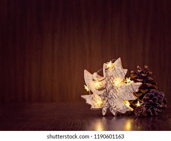 Simple, natural Christmas decor of pine cones with rustic maple leaf ornament wrapped in lights on a dark wood background.