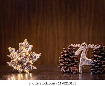 Simple, natural Christmas decor with rustic maple leaf ornament wrapped in lights on a dark wood background.