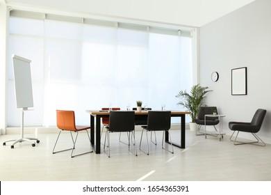 大きなテーブルと椅子を持つシンプルなオフィスの内部