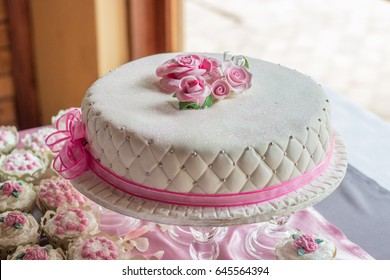 Simple one layer white wedding cake with pink roses and ribbon with smaller cupcakes on the side closeup