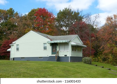 Simple one story home  with awnings and autumn foliage