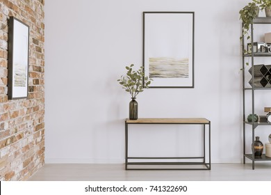 Simple painting above wooden console table with twigs in a glass vase in modern living room interior