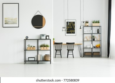 Simple painting and mirror on white wall above shelf in living room with black chairs at table