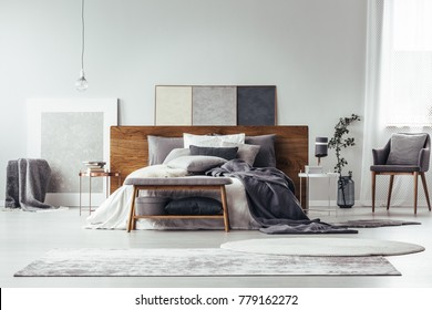 Simple painting on wooden bedhead of bed with pillows in grey bedroom interior with rugs, bench and chair