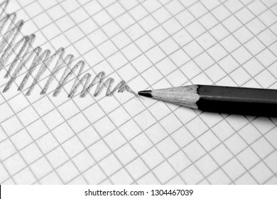 A simple pencil and hatching on the background of a checkered sheet of paper