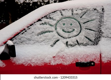 simple picture of a smiling sun carved in the snow upon a window of a red car