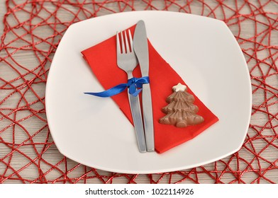 A simple place setting for Christmas consisting of a plate, fork, knife, red napkin and a chocolate shape christmas tree on a red place mat