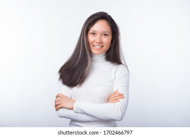 Simple portrait of an asian girl with arms crossed on white background.
