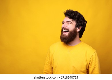 Simple portrait of a joyful man with large smile on yellow background.