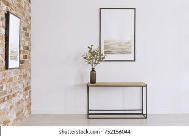 Simple poster on white wall above table with plant in black vase in art gallery