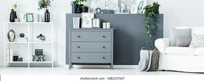 Simple posters, books and candles placed on grey cupboard standing in bright living room interior with white rack and decoration