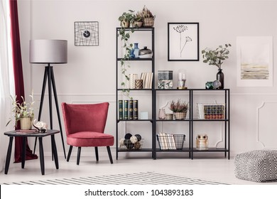 Simple posters hanging on white wall in hotel room interior with burgundy armchair