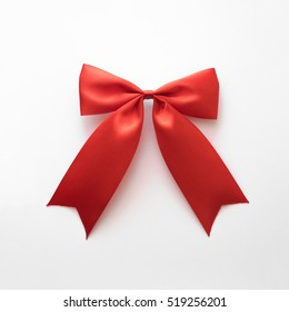 Simple red gift bow ribbon on white background. Real photography of red textile ribbon bow for gift.