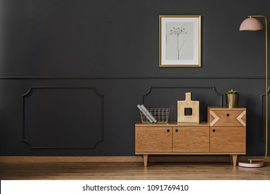 Simple retro living room interior with black walls, wooden floor, cupboard, lamp, ornaments and poster
