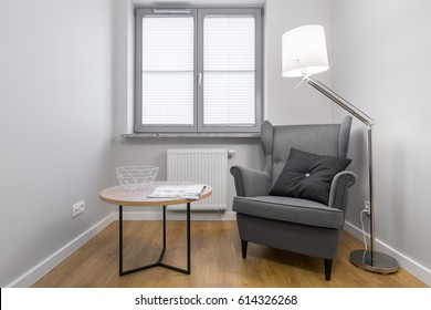 Simple room with grey armchair, round wooden table, stylish lamp and window