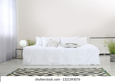 Simple room interior with large comfortable bed. Space for text