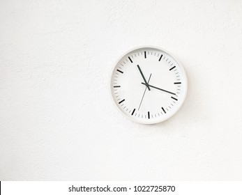Simple round clock on white wall. Contemporary home decor.