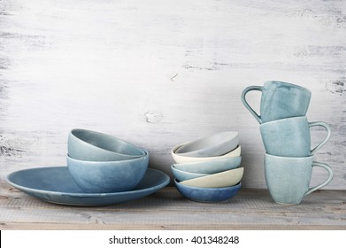 Simple rustic blue crockery against wooden wall: dish, stack of bowls and mugs.