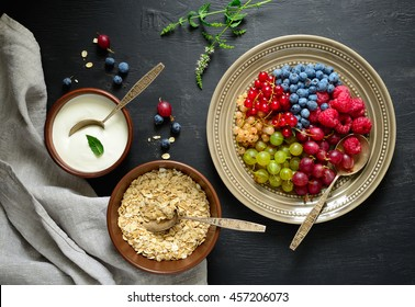 Simple rustic breakfast with various  garden berries, yogurt and oat granola, dark moody background, view from above
