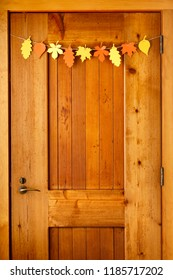 Simple, rustic country style Thanksgiving home decorations paper crafts garland banner colorful fall leaves on wooden front door background