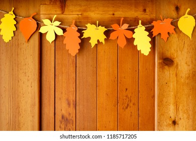 Simple, rustic country style Thanksgiving home decorations paper crafts garland banner colorful fall leaves on wood background