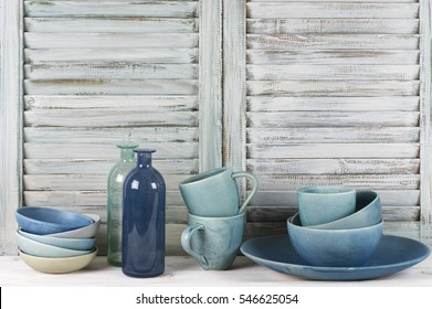 Simple rustic kitchen still life: handmade blue ceramic dish, bowls, mugs and glass bottles against shabby wooden shutters.