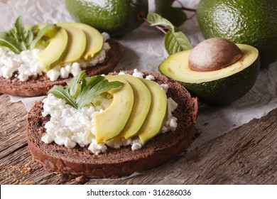 Simple sandwiches with avocado, cottage cheese and arugula close-up on the table. horizontal