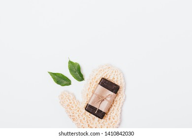 Simple set of basic hygiene items: bar of soap and washcloth on white background, flat lay.