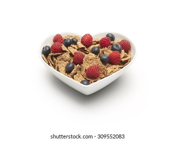 simple shot of bran flakes cereal with blueberries and strawberries added on a pure white background with copy space and a clipping path