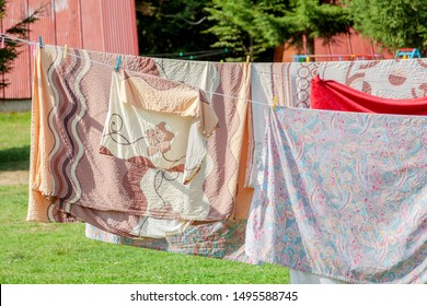Simple shot of laundry hanging, large bed set bedding and clothes hanging on wires on a sunny day, summer, drying outdoors, green neighborhood. Doing laundry and drying bedclothes, laundry day concept