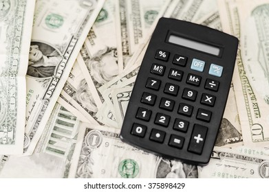 simple small black calculator isolated on dollar bills filling the frame.