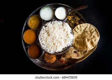 "Simple south Indian ""thali"" meal with fluffy white rice, a fried snack called ""papadum"", and six small round dishes of curries and vegetables on a large tin plate with black background"