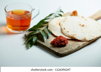 Simple Sri Lankan breakfast or snack of Pol Roti, Katta Sambol and Plain Tea on rustic wood with curry leaf on white background
