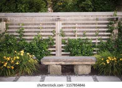 A simple stone bench between clusters of day lillies.
